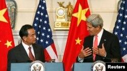 Menlu China Wang Yi (kiri) mendengarkan pernyataan Menlu AS John Kerry sebelum perundingan bilateral keduanya di Kemenlu AS, Washington DC, 19/9/2013.