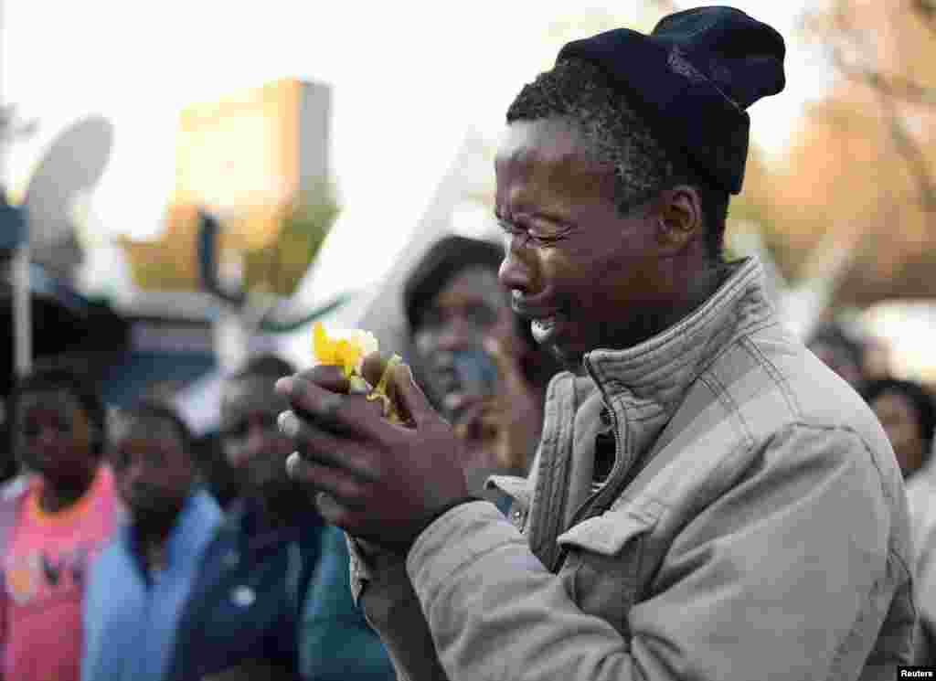 A well wisher weeps as he pays his respects outside the Mediclinic Heart Hospital, where ailing former South African President Nelson Mandela is being treated in Pretoria, July 1, 2013.