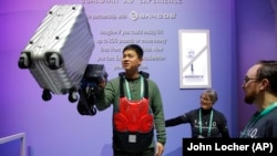 Eric Lynn lifts a 50 pound suitcase with the help of a powered arm similar to the Sarcos Robotics Guardian XO at the Delta Airlines booth during the CES tech show, Wednesday, Jan. 8, 2020, in Las Vegas.