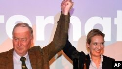 德国另类选择党(AfD)顶级候选人亚历山大·高兰(左)和爱丽丝·韦德尔在柏林举行的选举集会上与他们的支持者一起庆祝(2017年9月24日)。