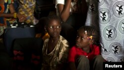 FILE - Children sit inside a container truck as they wait to depart to the west of the country towards the border with Cameroon, in a convoy escorted by African Union (AU) peacekeeping forces as they flee sectarian violence in Bangui, C.A.R.