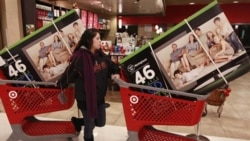A shopper in California guides her televisions out of a store last month