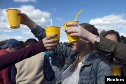 FILE - Revelers hold up yellow plastic cups during party in New Jersey, Oct. 17, 2015.