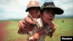 Hai bé trai đưa ra một viên đạn chưa nổ còn lại ở Khe Sanh từ thời chiến tranh Việt Nam
