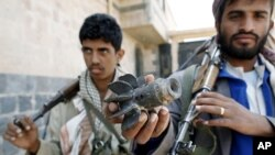 A Yemeni armed tribe member loyal to anti-government protesters displays remains of a projectile in the Al Nahda neighborhood of Sanaa September 24, 2011.