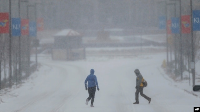 A jogger and pedestrian cross a snowy Jayhawk Boulevard on the University of Kansas campus in Lawrence, Kansas, Feb. 4, 2014.