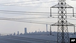 FILE - Electricity pylons cross the skyline of Johannesburg city, South Africa.