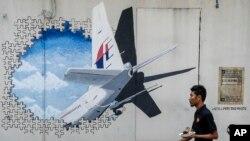Tư liệu - Người phục vụ bàn đi ngang một bức ảnh chiếc máy bay MH370 tại Shah Alam, ngoại ô Kuala Lumpur, Malaysia, ngày 23 tháng 02 năm 2016.