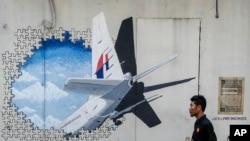 Seorang pria tengah berjalan melintasi lukisan mural dari pesawat Malaysia Ailines MH370 di Shah Alam, luar kota Kuala Lumpur, Malaysia. (Foto:AP Photo/Joshua Paul)