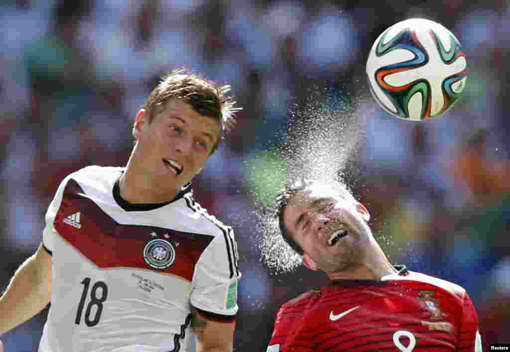 Germany's Toni Kroos (L) and Portugal's Joao Moutinho fight for the ball during their 2014 World Cup Group G soccer match at the Fonte Nova arena in Salvador, Brazil, June 16, 2014.