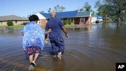 Sonya i Patrick King prolaze poplavljenom ulicom do svoje kuće u Lake Charlesu, (Foto: AP Gerald Herbert)