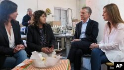 Argentina's President Mauricio Macri, Buenos Aires province governor Maria Eugenia Vidal, right, and Argentina's Minister of Social Development Carolina Stanley, left, talk to Lucila Godoy, president of the Osito Feliz textile factory, Sept. 18, 2017.