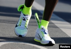 The insoles of Kenya's Eliud Kipchoge's running shoes are seen slipping up to his ankles, after he crosses the finish line to win the men's 42nd Berlin marathon, in Berlin, Germany, Sept. 27, 2015.