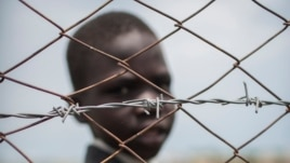 A young boy looks through the fence surrounding a safe place for children just outside Malakal. SOS Children's Villages says the children in its care need food and water, and aid agencies need more funds as food prices have spiked.