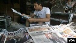Seorang penjual koran di kaki lima di Jakarta membaca dagangannya sembari menunggu pembeli (foto: dok).