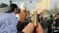 Một người biểu tình Ai Cập cầm 1 vỏ đạn trong cuộc biểu tình tại Quảng trường Tahrir ở Cairo, 19/12/2011