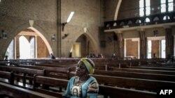 Une femme congolaise prie à la cathédrale Notre-Dame-de-Kinshasa de Kinshasa lors d'un service religieux le 29 décembre 2018.