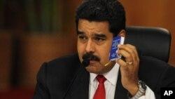 El presidente Nicolás Maduro muestra una copia miniatura de la Constitución, durante la reunión de diálogo con la oposición.