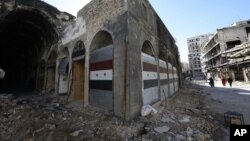 Damaged shops are seen with new doors in the old city of Homs, Syria on Tuesday, Dec. 8, 2015.