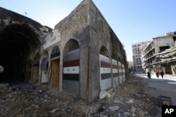 FILE - Damaged shops are seen with new doors in the old city of Homs, Syria on Tuesday, Dec. 8, 2015.