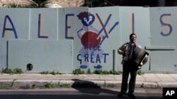 """Atina'nın turistik Plaka semtinde """"Büyük Alexis"""" yazılı duvar yazısının önünde akordeon çalan sokak çalgıcısı. Aleksis Çipras, kemer sıkma önlemlerinden bunalan Yunan halkının son umudu."""