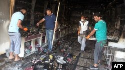 Iraqi men clear up a burned shop in Baghdad following two car bombs that were set off in mostly Shi'ite neighborhoods of the Iraqi capital, July 22, 2015.