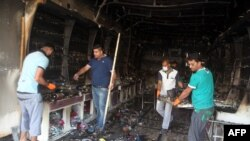 Warga Irak membersihkan kios yang terbakar akibat ledakan dua bom mobil di Baghdad, Rabu (22/7).