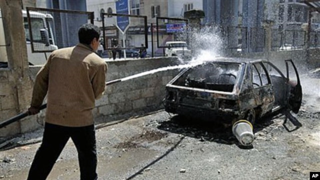 A Syrian municipality worker sprays water at a burnt car that was set on fire by Syrian anti-government protesters, in the southern city of Deraa, Syria, March 21, 2011