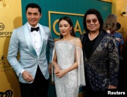 """Author Kevin Kwan (R) and cast members Henry Golding and Constance Wu pose at the premiere for """"Crazy Rich Asians"""" in Los Angeles, California, Aug. 7, 2018."""