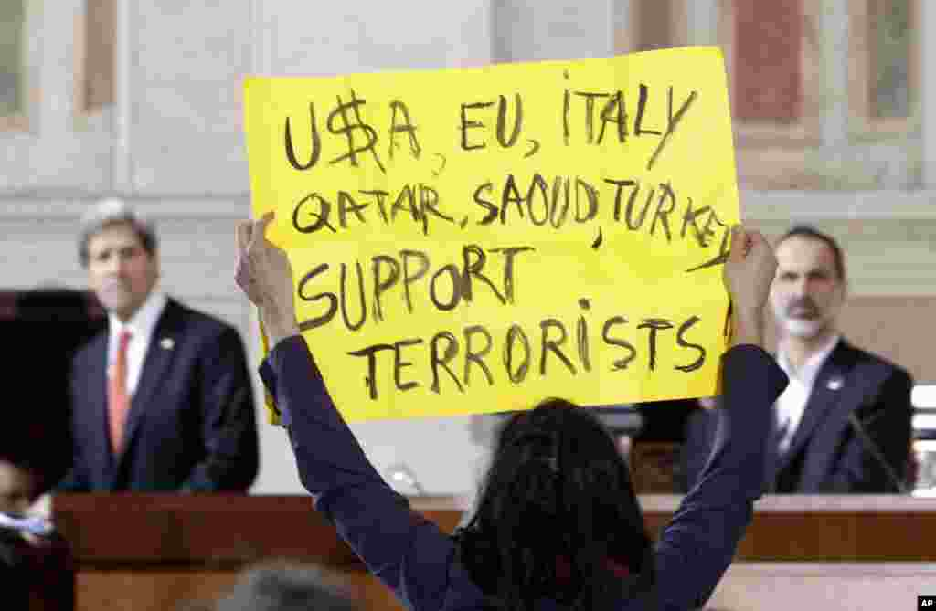 A peace activist protests at the end of statements given by U.S. Secretary of State John Kerry and Syrian National Coalition President Mouaz al-Khatib at Villa Madama in Rome, Feb. 28, 2013.