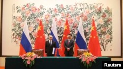 Presiden Rusia Vladimir Putin (kiri) dan Presiden China Xi Jinping saat menandatangani perjanjian kerjasama energi kedua negara di sela KTT APEC di Beijing, Minggu (9/11).
