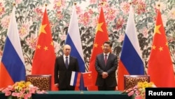 Russia's President Vladimir Putin (L) and his Chinese counterpart Xi Jinping stand during a signing ceremony at the Diaoyutai State Guesthouse in Beijing, Nov. 9, 2014.