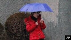 一名北韓婦女在平壤街頭使用手機。(資料圖片)
