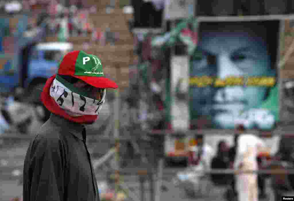 """A supporter of Imran Khan, the Chairman of the Pakistan Tehreek-e-Insaf (PTI) political party, with a party flag wrapped around his face stands during what has been dubbed a """"freedom march"""" in Islamabad."""