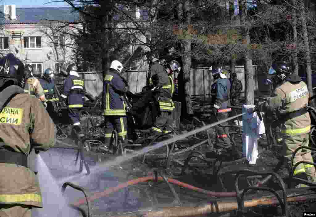 Russian emergency service staff spray water and remove remains at the site of a fire at a psychiatric hospital in the village of Ramensky, north of Moscow, April 26, 2013.