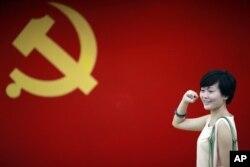 在上海的中共第一次代表大会会址,一名女子在中国共产党党旗下摆出宣誓姿势 (2012年7月1日)