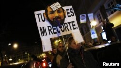 A demonstrator carries a sign with a mask resembling Spanish Prime Minister Mariano Rajoy, as they cut off traffic after a protest outside the headquarters of the ruling People's Party (Partido Popular) in Madrid, February 2, 2013.