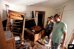 Smita Depani, center, checks out flood damage in her apartment in the Starlite Motel, which she co-owns with brother-in-law Jayanti Depani, right, and sister-in-law, Puspa Manvar, in Spring Lake, North Carolina, Sept. 19, 2018.