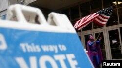 Lin Wilson mengibarkan bendera AS untuk mendorong orang-orang memilih pada hari pemilihan, di Seattle, Washington, AS, 3 November 2020. (Foto: REUTERS/Lindsey Wasson)