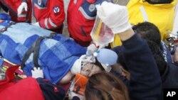 土耳其救援人員在凡市地震災區將從倒塌的建築物下救出的生還者送上救護車。