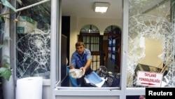 Seorang pria menyingkirkan batu-batu yang dilemparkan ke dalam konsulat Thailand di Istanbul, Turki (9/7).