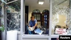 一名男子从泰国驻土耳其荣誉总领事馆搬走石块。(2015年7月9日)