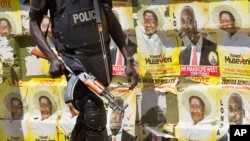 FILE - An armed Ugandan riot policeman is seen on patrol against the backdrop of campaign posters for long-time President Yoweri Museveni, as well as local members of Parliament, on a street in Kampala, Uganda, Feb. 17, 2016.