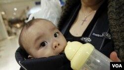 Miyako Ikeda memberi minum bayinya, Ryutaro, dengan air minum kemasan dari supermarket (foto: dok). Produsen makanan Jepang ternama menemukan kadar caesium rendah dalam produk susu bayi.
