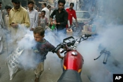 A boy tries to outrun a man fumigating for mosquitoes in an effort to combat dengue fever, on the streets of Lahore, Pakistan, Sept. 20, 2011.