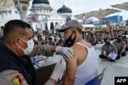 Seorang pria disuntik vaksin COVID-19 Sinovac di depan Masjid Agung Baiturrahman, Banda Aceh, 30 Maret 2021. (Foto: CHAIDEER MAHYUDDIN / AFP)