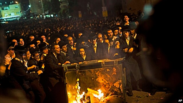 Ultra-orthodox Jews push a burning garbage bin towards Israeli security forces during a protest against military conscription of yeshiva students, in Jerusalem, May 16, 2013.