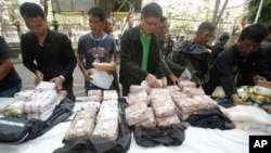 FILE - Thai policemen display intercepted drugs - 226 kilograms (498 pounds) of crystal meth and 8 kilograms (18 pounds) of heroin - during press a conference in Bangkok, Thailand, March 24, 2016. Thai police arrested 15 Malaysians as part of the heist.