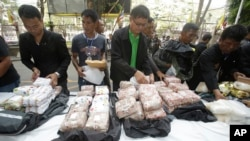 FILE - Thai policemen display intercepted drugs - 226 kilograms (498 pounds) of crystal meth and 8 kilograms (18 pounds) of heroin - during press a conference in Bangkok, Thailand.