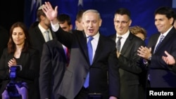 Israel's Prime Minister Benjamin Netanyahu waves to supporters as he stands with his party members at the Likud-Yisrael Beitenu headquarters in Tel Aviv January 23, 2013.